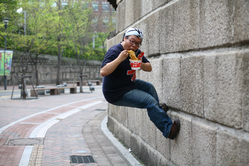 guy eating noodles out box while jumping wall